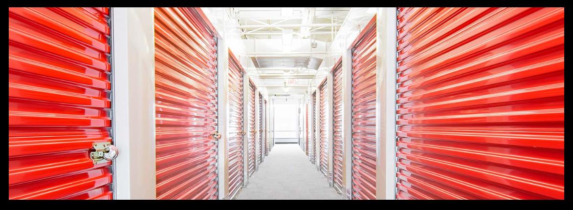 Self storage building with orange rolling doors.