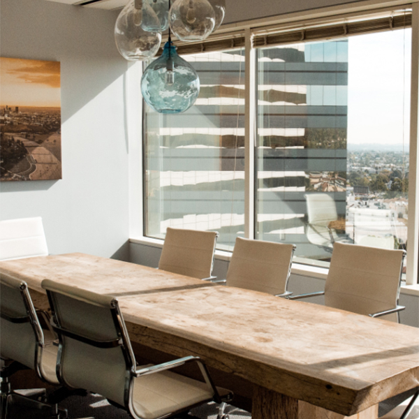 Conference room with large table, office chairs, chandelier, and large windows.
